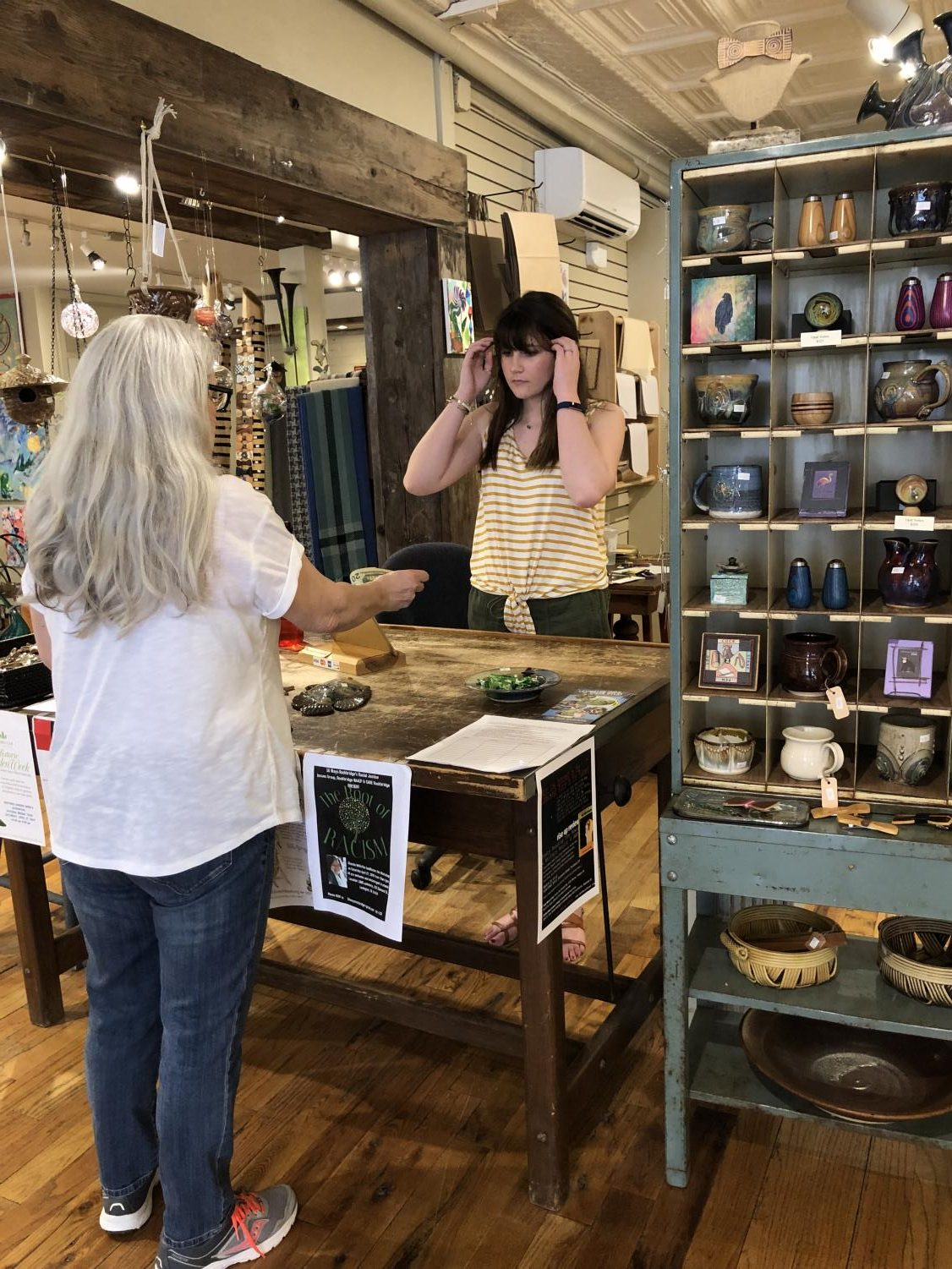 Savannah Webb checks out a customer purchasing a piece of pottery at Earth, Fire and Spirit Pottery Shop.