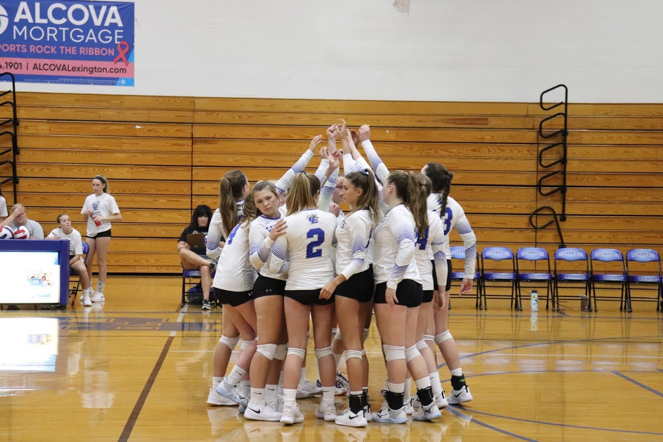 The volleyball team huddles up before the game.