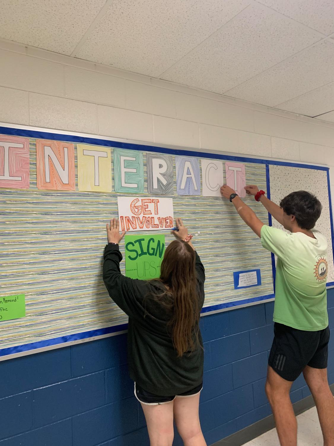 Co-presidents Margaret and Adam prepare posters for the Interact Board.
