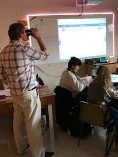 Earth Science teacher Aaron Grabinksi enjoys a sip of coffee while teaching his students work on a project.