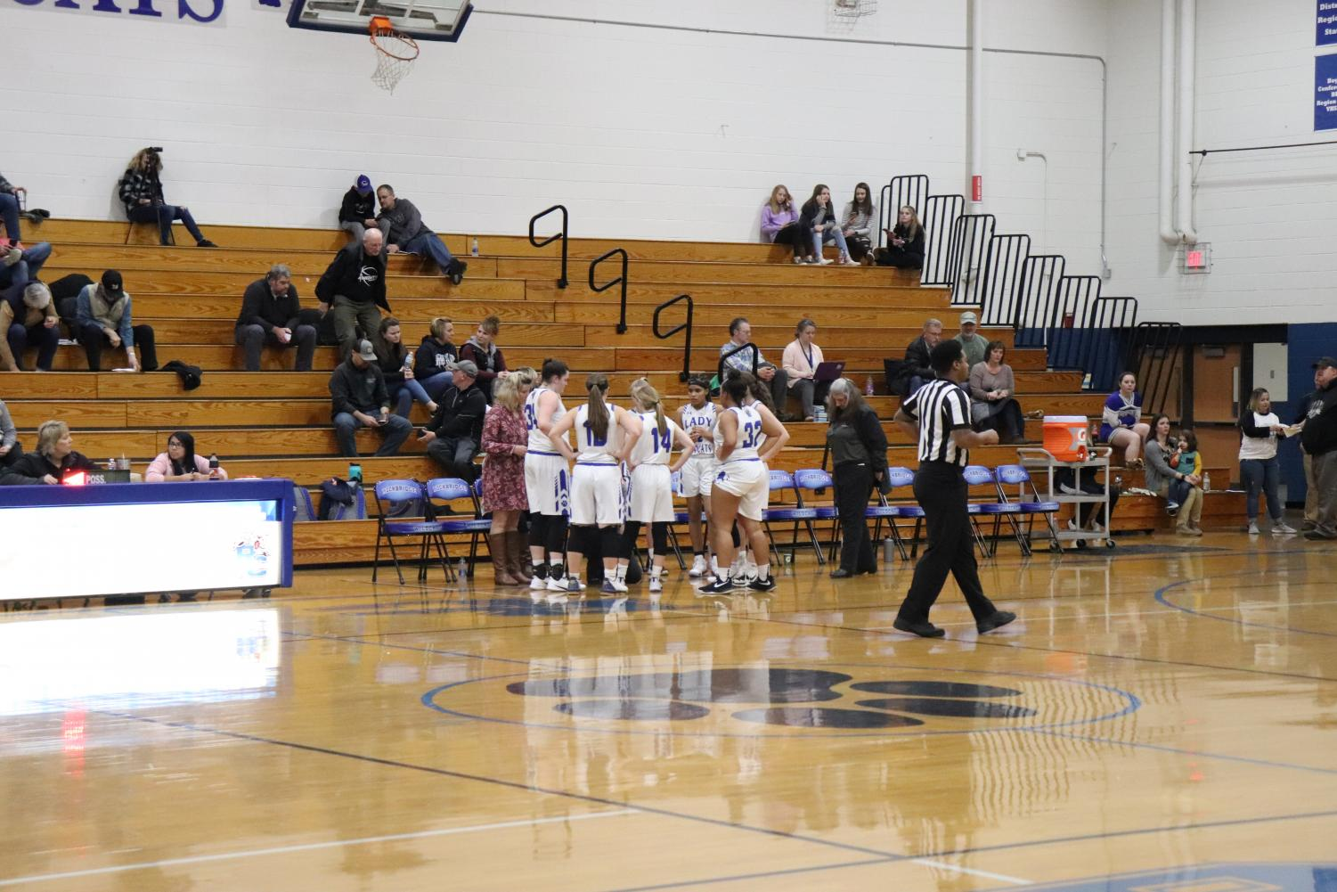 Girls team huddling in a timeout.