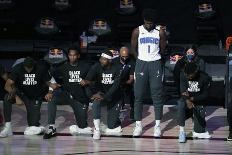 Jonathan Isaac decides to stand during the National Anthem and where his Orlando Magic jersey. Image from AP News.com